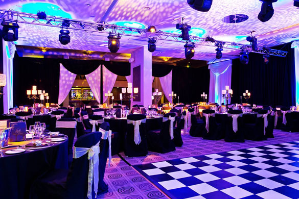 Full room draping with chair covers, centrepieces, a black and white dance floor for a corporate event.